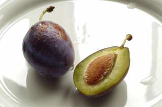 Whole plum and half with a bone on a plate
